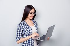 Smart and educated asian woman dressed in casual clotes is holdi. Ng laptop and writing new programe, she is it-specialist, isolated on grey background Stock Photo