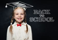 Smart educated school girl student in graduation hat. Doodle on blackboard background for children`s world literacy day and scholarship concept. Back to school stock images