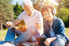 Smart elderly gentleman asking his grandson about his hobby Stock Photography