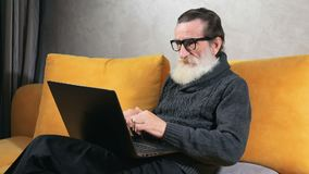 Elderly Man Types on Laptop. Smart elderly man in glasses typing on black laptop, surfing the internet to find necessary information on the topic, indoor shoot stock video