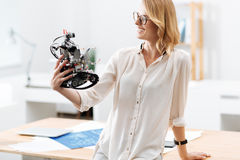 Smart engineer enjoying electronic robot functions in the laboratory. Looking into the future with confidence . Cheerful charming intelligent engineer working in Stock Photo