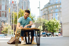Smart enterprising guy working outdoors. Free of office. Handsome enthusiastic positive man sitting on a terrace and enjoying the warm weather while having a Royalty Free Stock Images