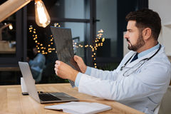 Smart experienced doctor putting a diagnosis. Professional diagnostician. Smart experienced handsome doctor studying an X ray image and putting a medical Royalty Free Stock Photos