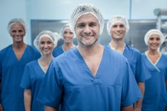 Smart experienced surgeon standing in front of his team. Team of surgeons. Smart experienced male surgeon standing in front of his team and looking at you while royalty free stock images
