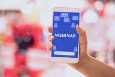 Smart för håll för hand för Webinar begreppskvinna som telefon direktanslutet e-lär på mobil, med blå bakgrunder, begrepp och exp arkivbild