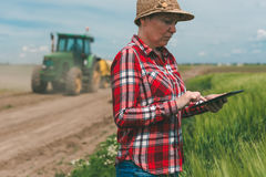 Smart farming, using modern technology in agricultural activity. Female farmer agronomist with digital tablet computer using mobile app in wheat crops field royalty free stock photography