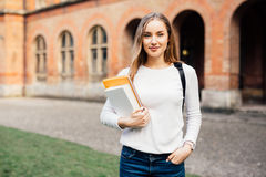 Smart female college student with bag and books on campus outdoors royalty free stock image