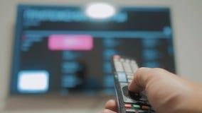 Smart-Fernsehen mit apps und der Hand Die männliche Hand, die den Fernsteuerungslebensstil hält, stellen intelligentes Fernsehen  stock video