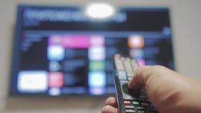 Smart-Fernsehen mit apps und der Hand Die männliche Hand, welche die Fernbedienung hält, drehen sich weg von intelligentem Lebens stock footage