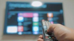 Smart-Fernsehen mit apps und der Hand Die männliche Hand, welche die Fernbedienung hält, stellen intelligentes Fernsehen des Lebe stock video