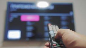 Smart-Fernsehen mit apps und der Hand Männliche Hand, die den Fernsteuerungsdrehungslebensstil weg von intelligentem Fernsehen hä stock video footage