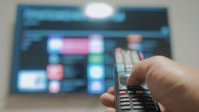 Smart-Fernsehen mit apps und der Hand Männliche Hand, die weg das intelligente Fernsehen der Fernbedienungsdrehung hält Mannhand  stock video footage