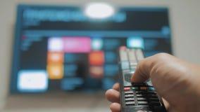 Smart-Fernsehen mit apps und der Hand Männliche Hand, die weg das intelligente Fernsehen der Fernbedienungsdrehung hält Mannhandl stock video