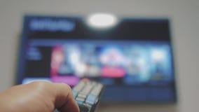 Smart-Fernsehen mit apps und der Hand Männliche Hand, die weg das intelligente Fernsehen der Fernbedienungsdrehung hält Mannleben stock video