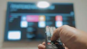 Smart-Fernsehen mit apps und der Hand Männlicher Handholdinglebensstil die Fernbedienungsdrehung weg von intelligentem Fernsehen  stock video