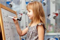 Smart flicka nära det vita brädet arkivbilder
