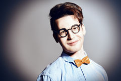Smart fun. Portrait of an extravagant young man in bow-tie and roung glasses posing at studio stock photo