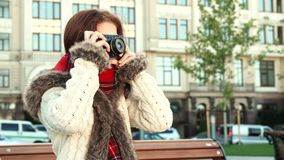 Smart girl adjusts the camera to take a picture. The girl is holding an old-fashioned camera in her hands. She twists it and presses the buttons to adjust it Royalty Free Stock Image