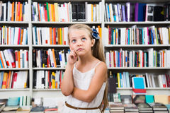 Smart girl child bemused a lot of books in a bookstore Royalty Free Stock Photo