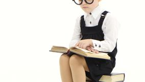 Smart girl in glasses studying an interesting book, white studio stock footage