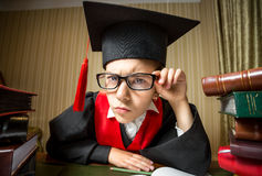 Smart girl in graduation cap and eyeglasses looking at camera Royalty Free Stock Images