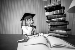 Smart girl in graduation cap looking at high heap of books Royalty Free Stock Images