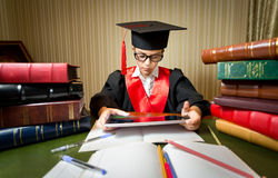 Smart girl in graduation cap playing on digital tablet Stock Photo