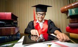 Smart girl in graduation cap using digital tablet at library Stock Image