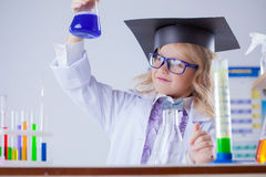 Smart girl looking at color of reagent in flask Royalty Free Stock Images