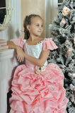 Smart girl in a pink dress by the fireplace Stock Images