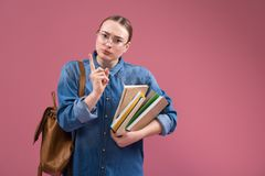 Smart girl prefers hones study. Do not cheat. Portrait of serious young woman warning by her finger. She is standing and holding books. Isolated and copy space stock images