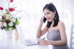 Smart girl`s using smart phone and working on laptop ,happy time. On work, smile and laughing time work , workingwomen get think about work Royalty Free Stock Image