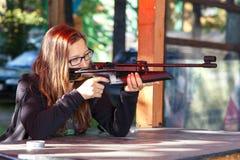 Smart girl shooting from air gun royalty free stock image