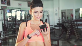 Smart girl taking funny selfies in a modern gym stock video footage