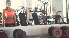 Smart girl training with dumb-bell in front of the mirror in the gym. In full HD stock footage