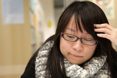 Smart girl who is thinking. She is a top student in University, thus she thinks deeply about the academic stuffs Stock Photo