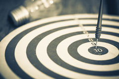 Smart Goal Setting. Dart hit the center of dartboard with light bulb on background royalty free stock photo