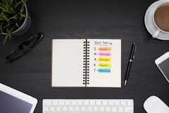 Smart goal setting on notebook over black table desk. Smart goal setting on notebook with office supplies, computer, eye glasses and coffee cup over black table royalty free stock image