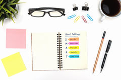 Smart goal setting with office supply over white desk. Smart goal setting on spiral notebook with pen, pencil, office supply, eye glasses and coffee cup over royalty free stock photography