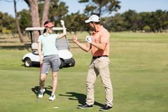 Smart golfer couple celebrating success. While standing on field Royalty Free Stock Photography