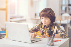 Smart good looking boy writing on sticky notes. Sticky notes. Smart cute good looking boy holding a pencil and writing on sticky notes while sitting in front of Stock Photography