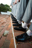 Smart groomsmen stood in row. Legs and feet of smart groomsmen stood in row at wedding in matching gray suits with black shoes and the same colored socks Royalty Free Stock Photos