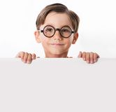 Smart guy. Face of youthful boy in glasses looking from behind white partition Stock Photography