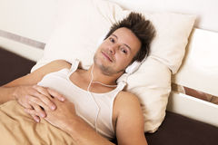 Smart guy lies in bed and listens to music Stock Image