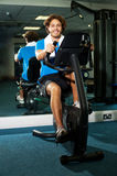 Smart guy working out in the exercise bike Stock Photography