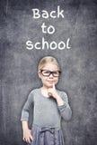 Smart härlig liten flicka på svart tavlabakgrunden arkivfoto