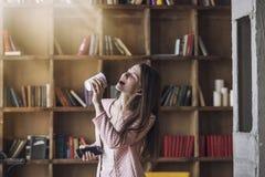 Smart härlig ung kvinna i hörlurar med ett exponeringsglas av kaffe arkivbild