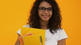 Smart högskolestudent i glasögon som rymmer böcker gul bakgrund, utbildning arkivfilmer