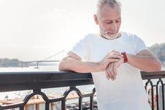 Smart ha invecchiato l'uomo che sta e che esamina il suo orologio immagini stock libere da diritti