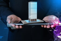 Smart hand showing smart phone with real estate concept Stock Image